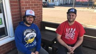 Deux frères assis sur une terrasse extérieure.
