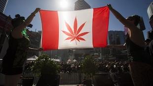 Deux femmes tiennent un drapeau du Canada où la feuille d'érable a été remplacée par celle de la marijuana
