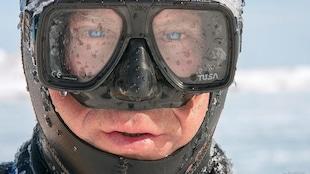 Le photographe Mario Cyr portant un masque de plongée, tout glacé.