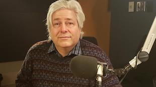 Un homme aux cheveux grissonnant souriant dans un studio de radio.