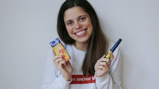 Une jeune femme pose devant un mur avec un cocktail aux pêches dans une main et une seringue d'insuline dans l'autre.