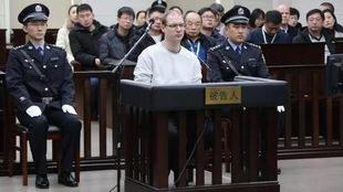 Le canadien Robert Lloyd Schellenberg est assis dans le box des accusés flanqué de deux policiers chinois.