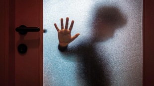 Un enfant derrière une fenêtre givrée dépose sa main contre la vitre et regarde au sol.