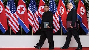 Kim Jong-un et Donald Trump tiennent des documents de l'entente sur la dénucléarisation de la péninsule coréenne et marchent devant des drapeaux de leur pays respectif.