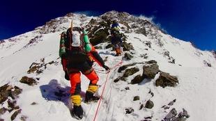 Des alpinistes encordés gravissent le flanc d'une montagne enneigée.