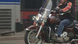Un homme roule sur une moto rouge. On ne voit pas son visage.
