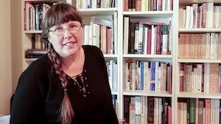 L'écrivaine Mylène Gilbert-Dumas pose devant une bibliothèque, dans son bureau.