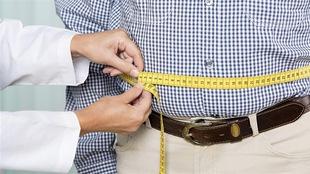 Un médecin mesure le tour de taille d'un homme.