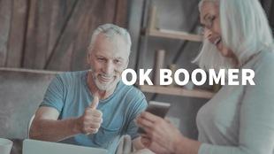 Un homme âgé fait un pouce en l'air devant un téléphone intelligent tenu par une femme. Le titre OK Boomer est par-dessus la photo.