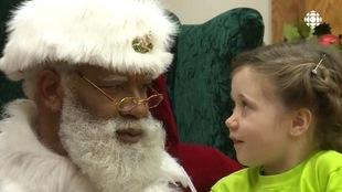 Un père Noël noir s'entretient avec une petite fille.