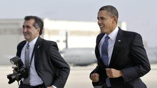 Barack Obama en train de courir dans un habit veston-cravate sur la piste d'aterrissage d'un aéroport en compagnie de Pete Souza, qui tient un appareil photo à la main.