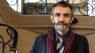 Le journaliste pose devant des escaliers recouverts d'un tapis rouge. Sa barbe poivre et sel cache ses blessures au visage. Il porte un veston bleu et un foulard rouge.