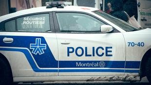 Plan moyen d'une auto-patrouille du Service de police de la Ville de Montréal (SPVM), vue sur le côté, en hiver.