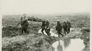 Des soldats marchent dans la boue, transportant un blessé.