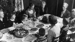Une famille prie avant le repas des Fêtes.