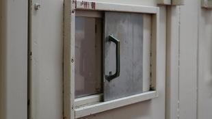 La porte comporte une petite fenêtre coulissante