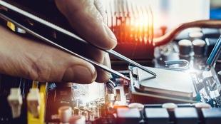 Un gros plan sur la main d'un homme en train de placer un processeur sur la carte mère d'un ordinateur à l'aide d'une petite pince en métal.