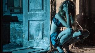 Une jeune femme légèrement vêtue accroupie sur le trottoir