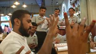 Des serveurs réunis autour d'un table discutent en utilisant la langue des signes