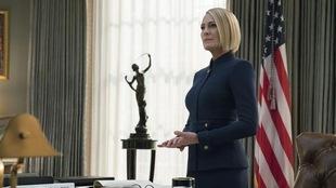 La femme est debout dans un bureau proche du drapeau américain.