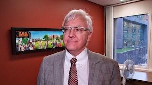 Un homme en entrevue devant un tableau «S.O.S. Monfort».