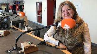 Portrait d'une femme dans un studio de radio. Elle est debout derrière une table sur lequel sont installés plusieurs micros.