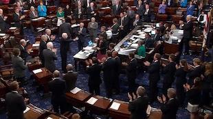 Le sénateur John McCain est applaudi par ses collègues à son retour au Sénat.