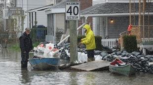 Des sinistrés près de barques, de sacs de sable et de maisons