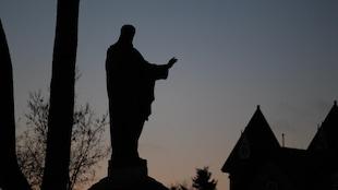 Une statue de Jésus, à contre-jour lors du coucher du soleil fin novembre. Le ciel est gris et dégagé
