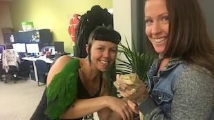 Deux femmes sourient à la caméra en tenant leurs animaux de compagnie exotiques, un perroquet et un dragon barbu.