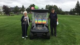 Deux personnes âgées posent de chaque côté d'un kart de golf qui affiche le nombre 188.