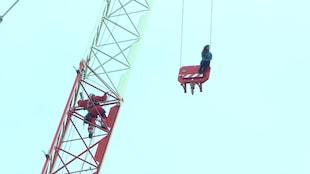 Photo du pompier qui grimpe dans la tour de la grue alors que la femme est assise sur le treuil.