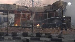 Pompier arrosant les décombres d'un immeuble incendié.