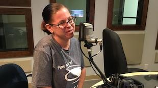 Valérie Héroux parle au micro dans le studio de radio.