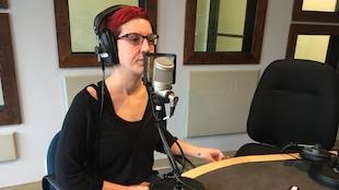 Véronique Aubin parle au micro dans le studio de radio.