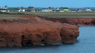 Une berge sablonneuse des Îles-de-la-Madeleine avec des maisons colorés en arrière plan.