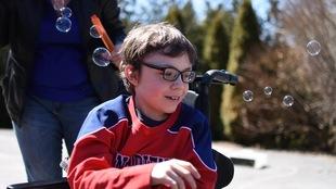Un petit garçon qui porte des lunettes est assis dans un fauteuil roulant.