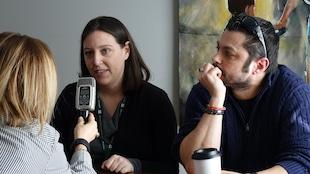 Un couple est assis à une table, en entrevue avec l'animatrice Jhade Montpetit qui tient un micro.