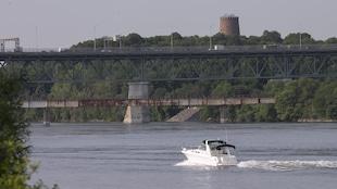 Un bateau de plaisance passe devant l'île Sainte-Hélène, à Montréal, sur le fleuve Saint-Laurent.