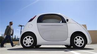 Un homme passe à côté d'une petite voiture blanche