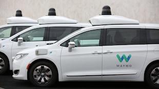 Une photo montrant trois mini fourgonnettes blanches portant le logo de Waymo sur l'une de leurs portes.