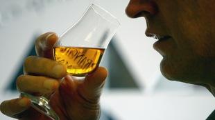 Un homme s'apprête à boire une gorgée de son verre de whisky.
