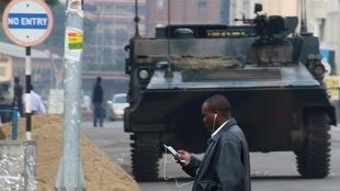 Un homme traverse une rue de la capitale du Zimbabwe, Harare, devant un char d'assaut de l'armée.