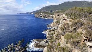 Extérieur. Jour. Vue aérienne sur des falaises qui plongent dans la mer d'un bleu profond.