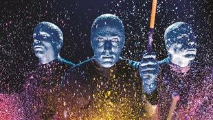 Trois hommes vêtus de bleu éclaboussent de la peinture en tapant sur des tambours.