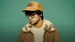Pierre Guitard portant des lunettes et une casquette devant un mur vert