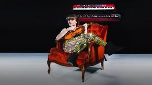 Vaero, installée sur un divan en velours rouge. Elle tient un violon comme si c'était une guitare. Deux claviers semblent flotter derrière elle. Le fond est noir et le sol est gris.