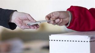 Début du vote par anticipation aux élections provinciales en Colombie-Britannique, un bulletin de vote et deux mains.