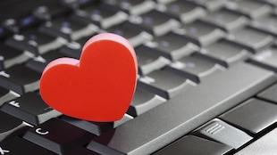 Un cœur rouge posé sur un clavier d'ordinateur.
