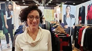 créatrice de mode métis devant son stand de vêtements